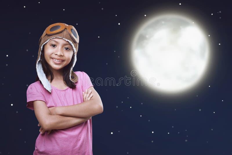 O tampão vestindo do aviador da criança asiática alegre e googles a posição sobre fotos de stock royalty free