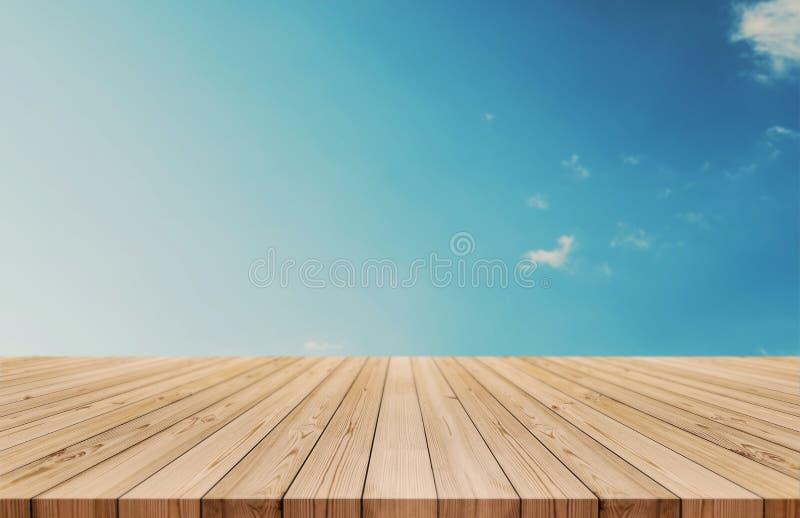 O tampo da mesa de madeira no céu azul e no branco do inclinação nubla-se o fundo igualmente usado para a exposição ou a montagem imagem de stock