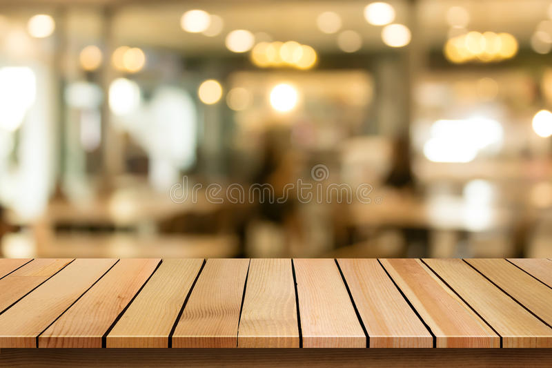O tampo da mesa de madeira no fundo do café do bokeh do borrão pode ser usado para o dis fotografia de stock