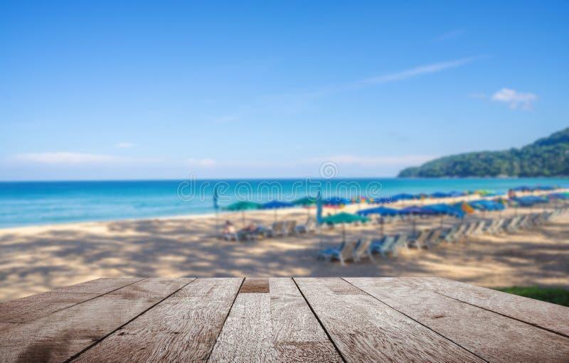 O tampo da mesa de madeira no parasol borrado e alguns povos relaxam na praia branca da areia e no mar azul com céu azul fotos de stock