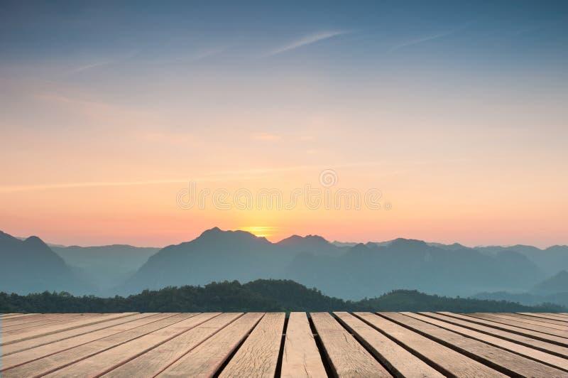 O tampo da mesa de madeira no por do sol majestoso nas montanhas ajardina imagem de stock
