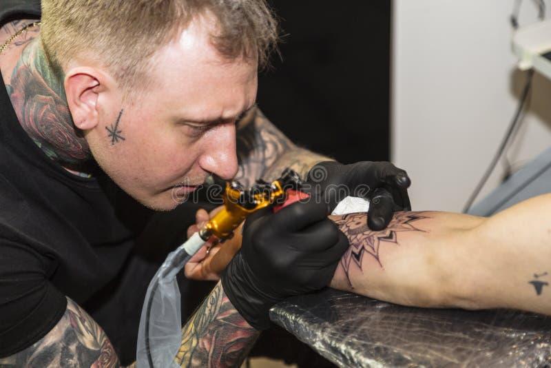 O Tattooist faz uma tatuagem em equipa o fim da mão acima foto de stock