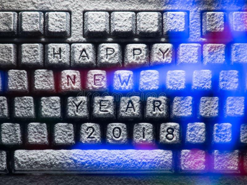 O teclado coberto com a neve com ano novo feliz 2018 do título iluminou-se por luzes coloridas fotografia de stock royalty free