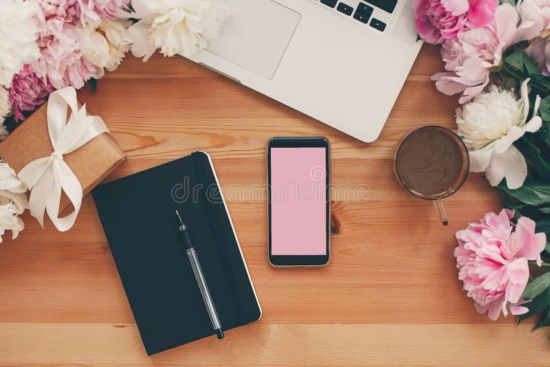 O telefone à moda com tela vazia, portátil, copo de café, caderno, presente com as peônias cor-de-rosa e brancas no plano da tabe fotos de stock royalty free