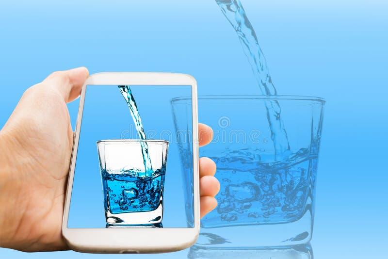 O telefone celular branco do punho derramou um vidro de ideias do conceito da água foto de stock royalty free