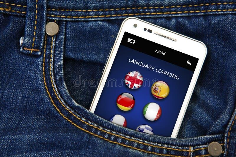 O telefone celular com aplicação do aprendizado de línguas nas calças de brim pocket fotos de stock royalty free