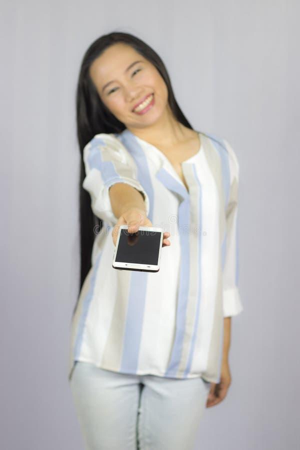 O telefone celular de sorriso da terra arrendada das mulheres, d?-lhe um telefone esperto Isolado no fundo cinzento foto de stock