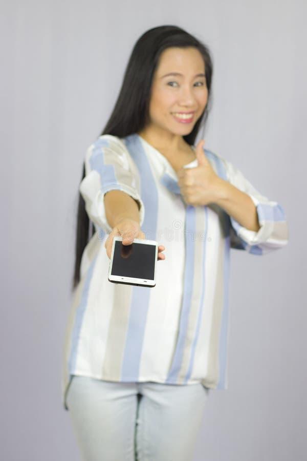 O telefone celular de sorriso da terra arrendada das mulheres, d?-lhe um telefone esperto Isolado no fundo cinzento fotografia de stock royalty free