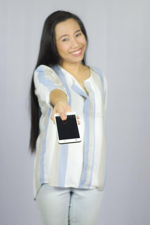 O telefone celular de sorriso da terra arrendada das mulheres, d?-lhe um telefone esperto Isolado no fundo cinzento fotografia de stock