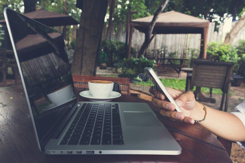 O telefone celular do uso da mão da mulher com vintage do portátil e do café tonifica fotos de stock royalty free
