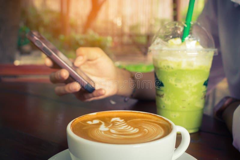 O telefone celular do uso da mulher e o frappe do chá verde da bebida com vintage do copo de café tonificam imagem de stock
