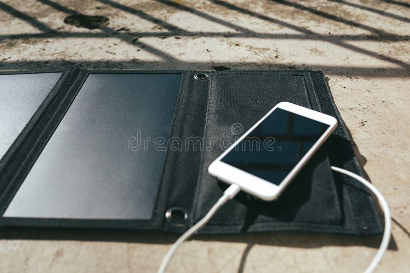 O telefone celular está carregando do painel solar imagem de stock