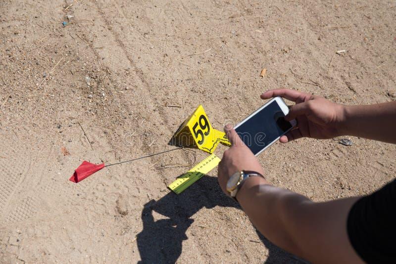 O telefone celular judicial do uso da mão toma a imagem da evidência com evi foto de stock royalty free