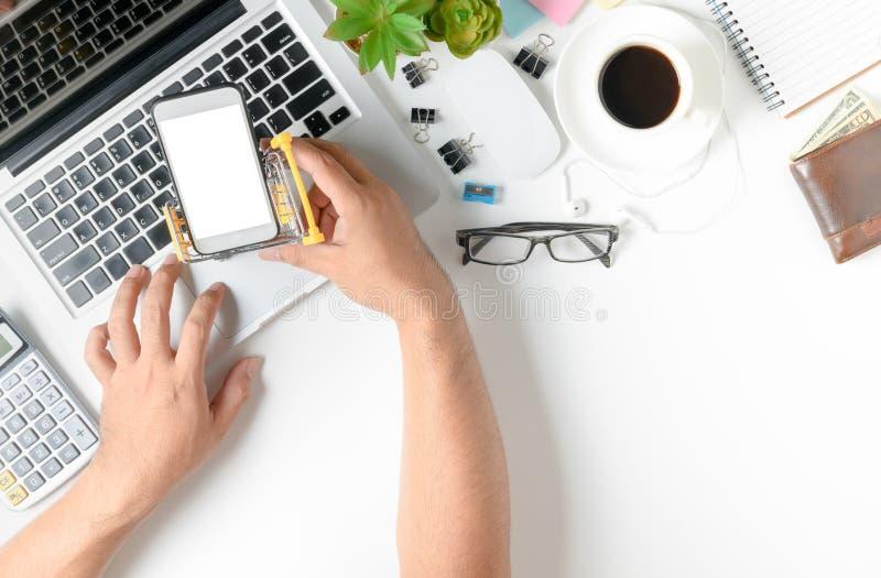 O telefone celular na compra do carro e a mão equipam usando o portátil fotos de stock