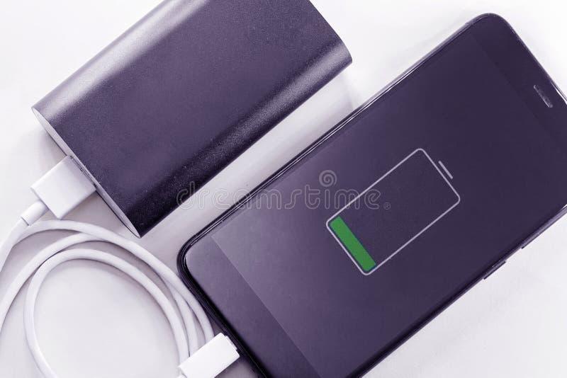 O telefone de Smartphone est? carregando do banco do poder fotos de stock royalty free