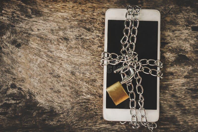 O telefone esperto com corrente e destrava o cadeado na tabela de madeira, conceito inseguro móvel da segurança fotos de stock royalty free