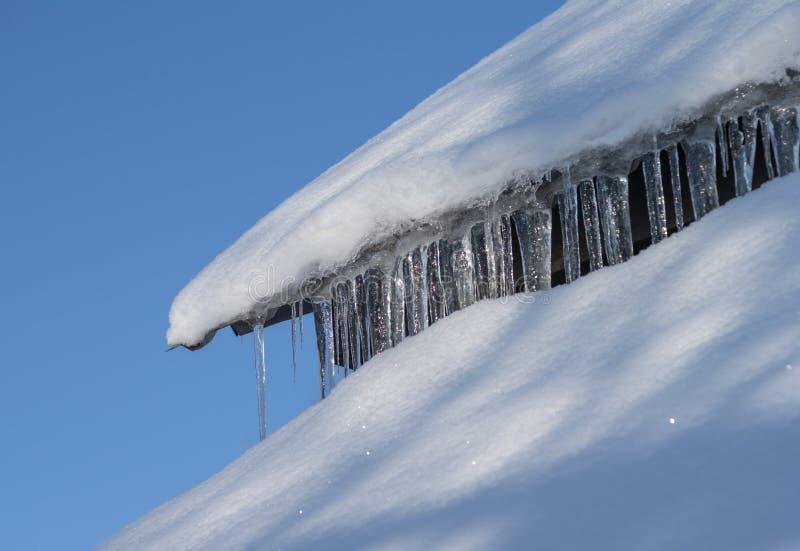 O telhado da casa coberta com a neve e os sincelos de suspensão foto de stock royalty free