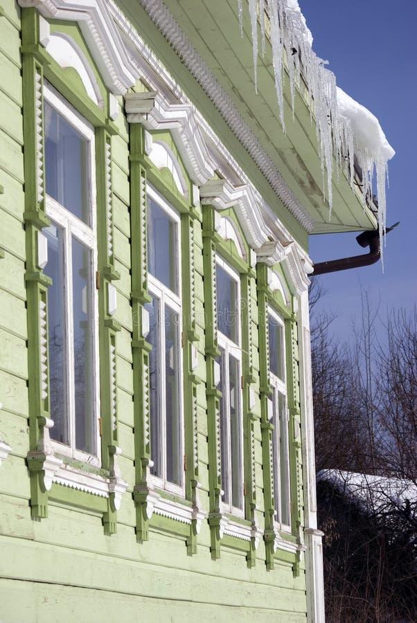 O telhado de uma casa de madeira do condado é coberto por sincelos imagens de stock royalty free