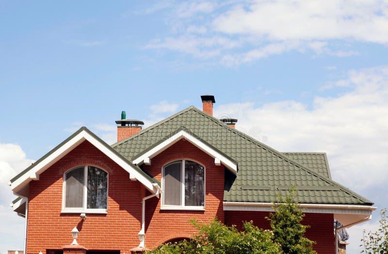 O telhado verde da casa bonita com janela e o azul agradáveis fotos de stock royalty free