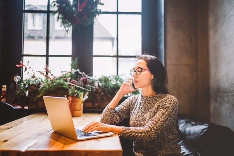 O tema é empresa de pequeno porte Uma mulher autônomo nova que trabalha atrás de um laptop em uma cafetaria decorada com decoraçã foto de stock royalty free