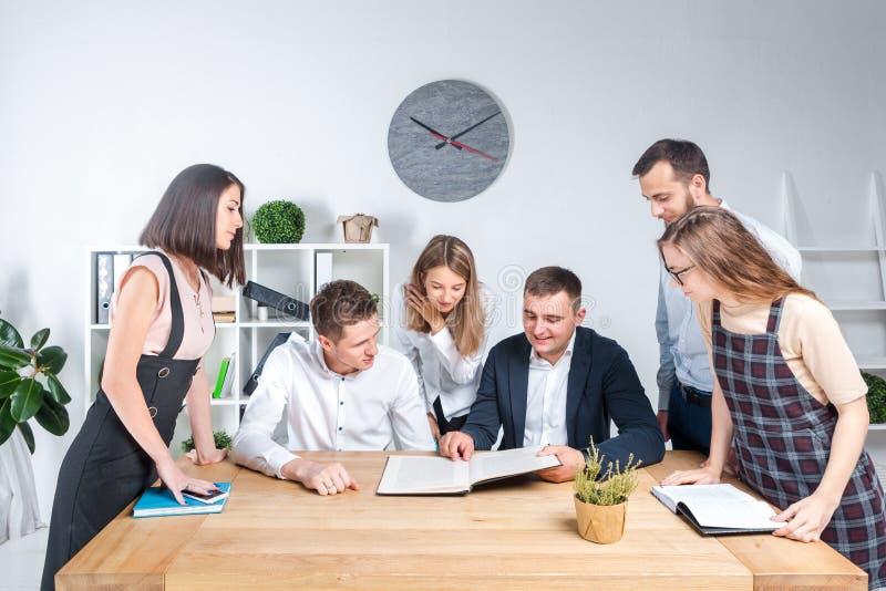O tema é negócio e trabalhos de equipe Um grupo de trabalhadores de escritório caucasianos novos dos povos que realizam uma reuni imagem de stock royalty free