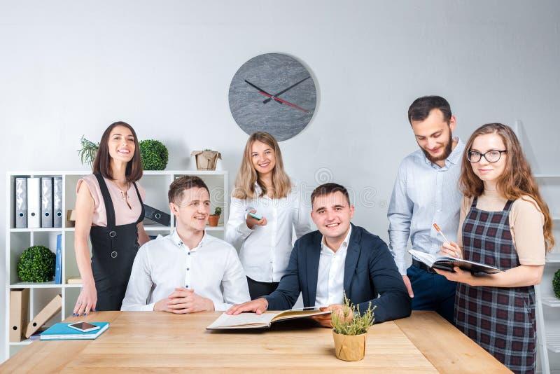 O tema é negócio e trabalhos de equipe Um grupo de trabalhadores de escritório caucasianos novos dos povos que realizam uma reuni foto de stock royalty free