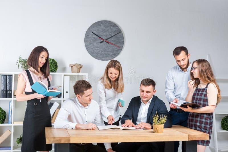 O tema é negócio e trabalhos de equipe Um grupo de trabalhadores de escritório caucasianos novos dos povos que realizam uma reuni imagem de stock