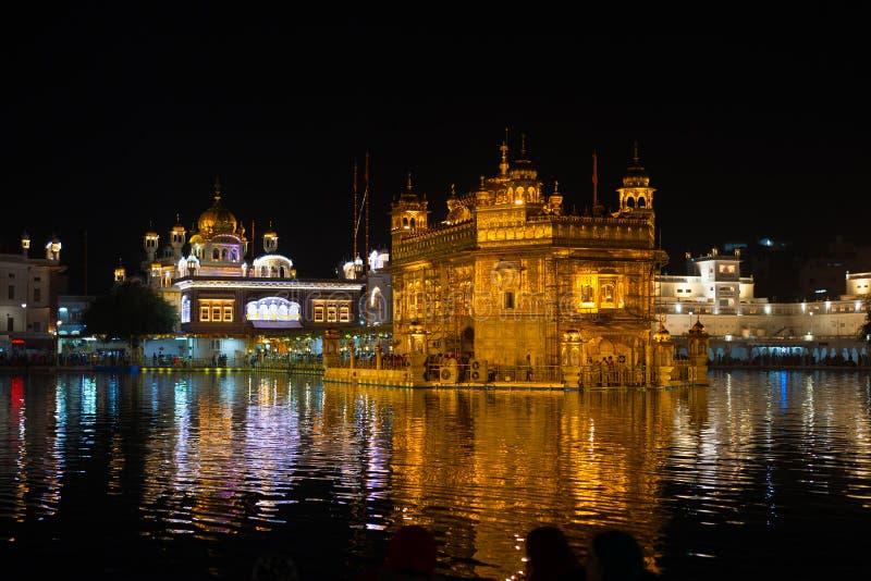 O templo dourado em Amritsar, em Punjab, em Índia, no ícone o mais sagrado e no lugar da adoração da religião sikh Iluminado na n imagens de stock