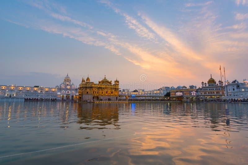 O templo dourado em Amritsar, em Punjab, em Índia, no ícone o mais sagrado e no lugar da adoração da religião sikh Luz do por do  fotos de stock
