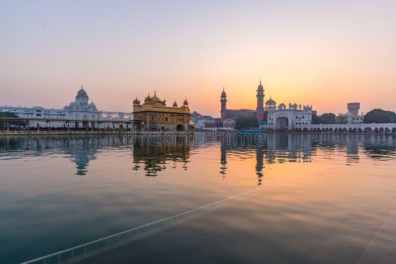 O templo dourado em Amritsar, em Punjab, em Índia, no ícone o mais sagrado e no lugar da adoração da religião sikh Luz do por do  imagens de stock royalty free