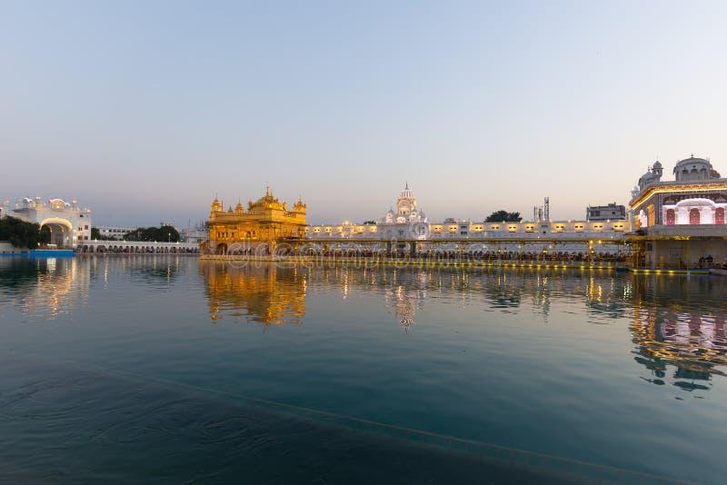 O templo dourado em Amritsar, em Punjab, em Índia, no ícone o mais sagrado e no lugar da adoração da religião sikh Luz do por do  fotografia de stock royalty free