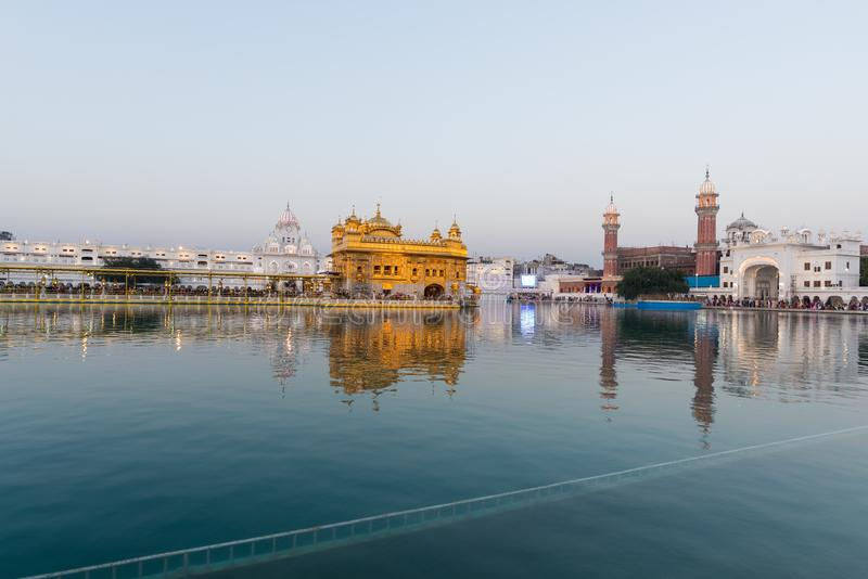 O templo dourado em Amritsar, em Punjab, em Índia, no ícone o mais sagrado e no lugar da adoração da religião sikh Luz do por do  imagem de stock royalty free