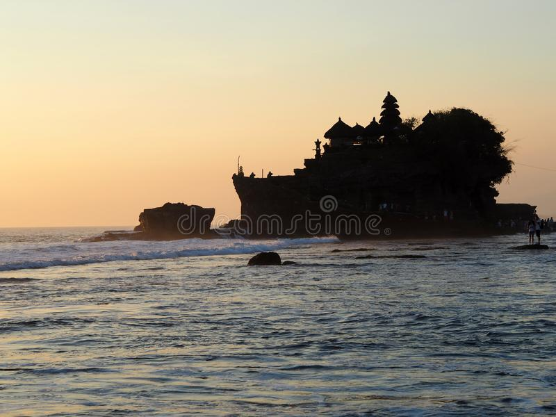 O templo famoso construído em uma rocha no lote de Tanah do mar no por do sol no Bal, Indonésia fotos de stock
