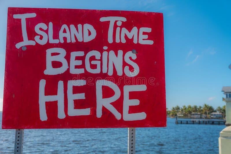 O tempo da ilha começa aqui - o sinal vermelho com rotulação branca fotografia de stock