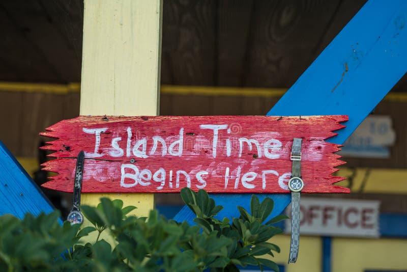 O tempo da ilha começa aqui - o sinal vermelho com rotulação branca imagens de stock royalty free