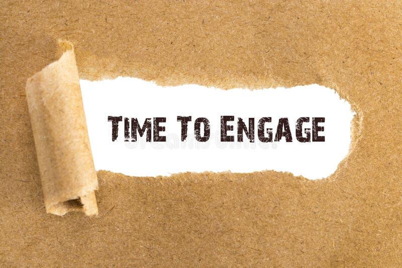 O tempo do texto Engage que aparece atrás do papel marrom rasgado imagem de stock
