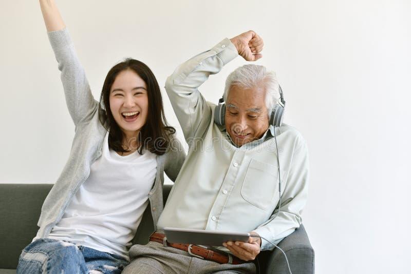 O tempo feliz da família, a filha asiática de sorriso e o pai idoso apreciam olhar o filme do tablet pc junto foto de stock royalty free