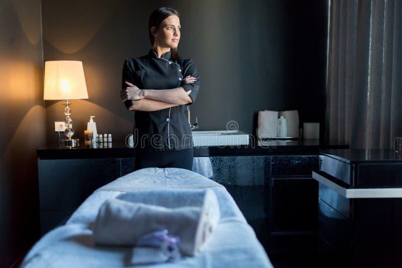 O terapeuta da massagem que está pelo tavle do bassage com mãos cruzou a fotos de stock royalty free