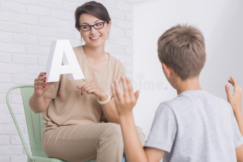 O terapeuta de discurso agradável ajuda o menino imagens de stock royalty free