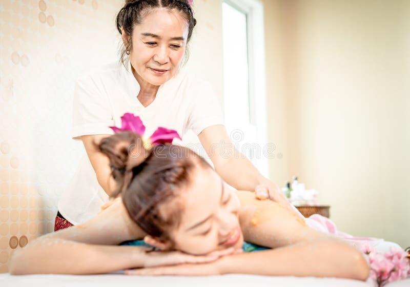 O terapeuta tailandês dos termas que dá a pele esfrega em uma parte traseira da mulher fotografia de stock royalty free