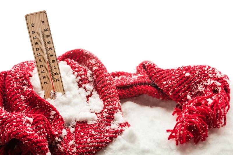 O termômetro com temperatura zero secundária cola para fora em um lenço vermelho envolvido monte de neve foto de stock royalty free