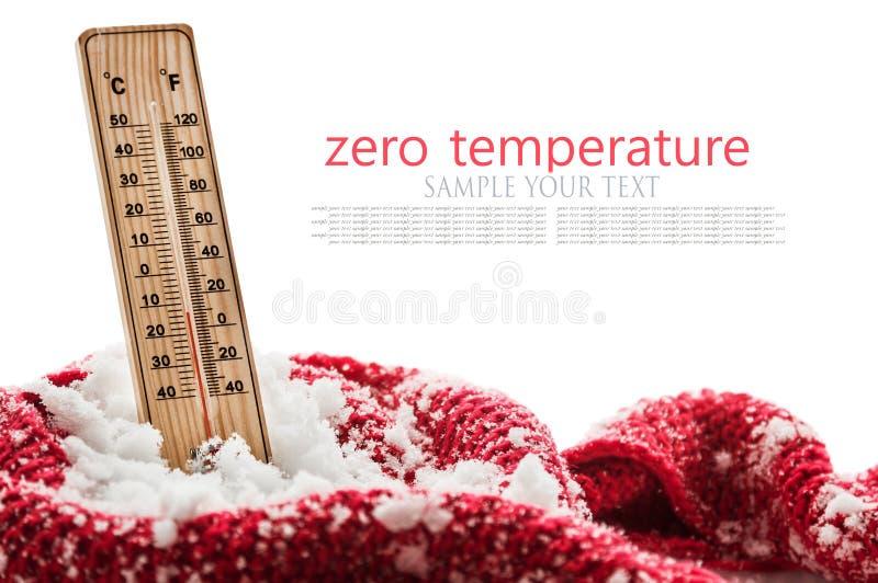 O termômetro com temperatura zero secundária cola para fora em um lenço vermelho envolvido monte de neve foto de stock