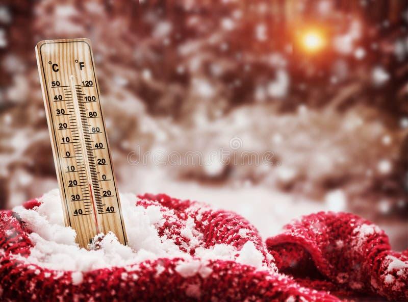 O termômetro com temperatura zero secundária cola para fora em um monte de neve envolvido imagens de stock royalty free