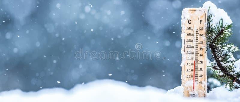 O termômetro na neve mostra baixas temperaturas em Célsio ou no farenheit fotografia de stock