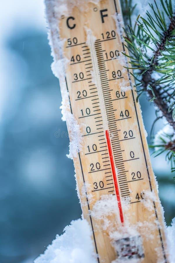 O termômetro na neve mostra baixas temperaturas em Célsio ou no farenheit imagem de stock