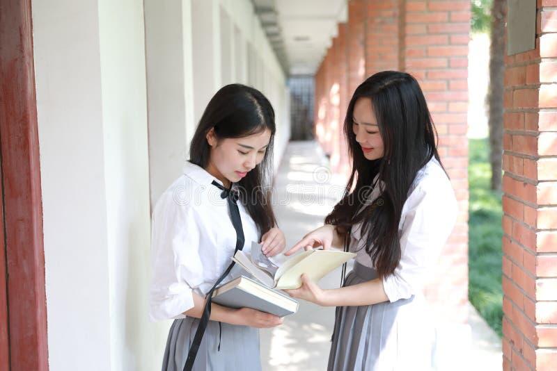 O terno bonito chinês asiático bonito do estudante do desgaste de duas meninas em melhores amigos da escola sorri livro de leitur fotografia de stock