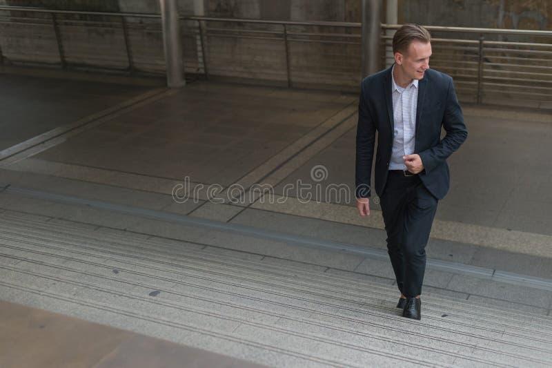 O terno do preto do desgaste do homem de negócios que anda intensificando a escada na cidade moderna, negócio cresce acima e conc fotografia de stock royalty free