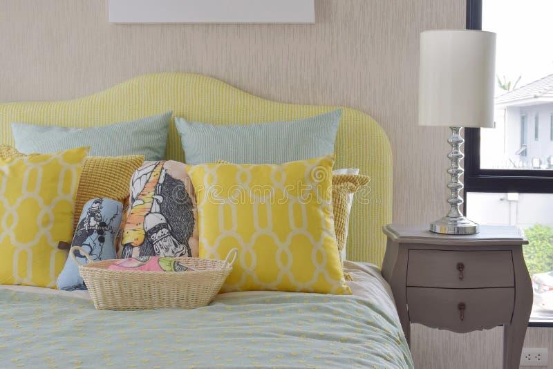 O teste padrão amarelo e verde descansa na cama clássica do estilo foto de stock