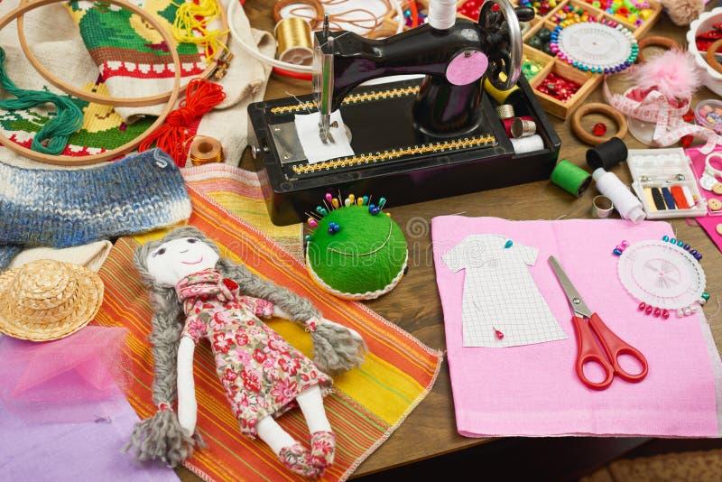 O teste padrão feito a mão da boneca e da roupa, costurando acessórios vista superior, local de trabalho da costureira, muitos ob fotos de stock royalty free