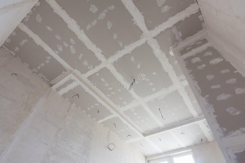 O teto da sala, coberto com as folhas da placa de gesso, e os pontos da massa de vidraceiro fotos de stock